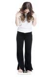 Ung flickaanseende på vågen som mäter vikt Fotografering för Bildbyråer