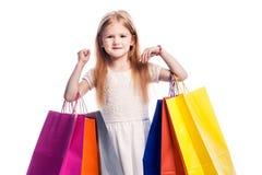Ung flickabarn som rymmer färgglade shoppingpåsar arkivfoton