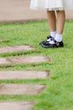 Ung flickaben med vitsockor och svarta skor står på gren Arkivfoto