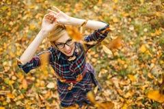 Ung flickadansen under fallande sidor i hösten parkerar Arkivfoton