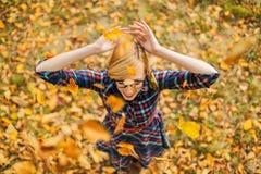 Ung flickadansen under fallande sidor i hösten parkerar Arkivbilder