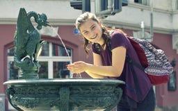 Ung flickadricksvatten från springbrunnen Fotografering för Bildbyråer
