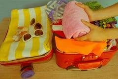 Ung flickaemballageresväska Kvinnaemballagematerial in i resväskan hemma Lopp- och semesterbegrepp Royaltyfria Bilder