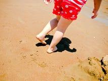 Ung flickafoten och lägger benen på ryggen att gå på stranden Royaltyfria Foton