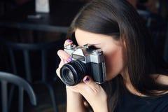 Ung flickafotograf med den gamla parallella kameran i kafé Arkivfoton