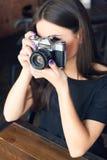 Ung flickafotograf med den gamla parallella kameran i kafé Royaltyfria Bilder