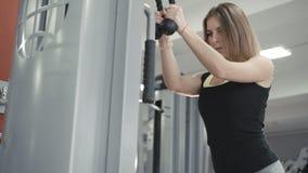 Ung flickagenomkörare med idrottshallsimulatorn för biceps i 4K lager videofilmer