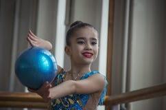 Ung flickagymnast med en blå boll i korridoren royaltyfri foto