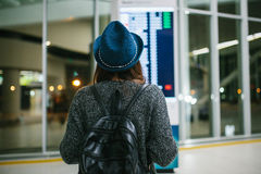 Ung flickahandelsresanden med en ryggsäck i en hatt ser informationsbrädet på flygplatsen Få information om royaltyfri bild