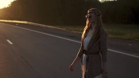 Ung flickahipster som promenerar vägen och beundrar soluppgången stående av solglasögon för en hippie för ung kvinna långsamt stock video