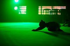 Ung flickaidrottsman nengymnasten utför akrobatiska beståndsdelar i ett grönt sceniskt ljus arkivbilder