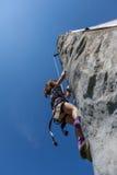 Ung flickaklättringen på den vertikala väggen med rep värme utomhus sommardag Royaltyfria Bilder