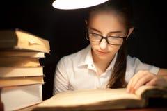 Ung flickaläsebok under lampan Arkivbild