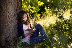 Ung flickaläsning bredvid ett stort träd royaltyfria foton