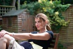 Ung flickaläsning i trädgården royaltyfria bilder