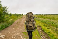 Ung flickalopp med den stora gröna ryggsäcken och metspöet i den arkivbilder
