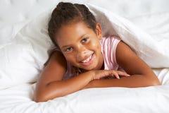 Ung flickanederlag under duntäcket i säng Arkivbild