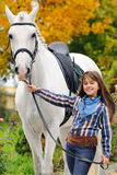 Ung flickaridning på den vita dressyrhästen royaltyfri foto