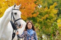 Ung flickaridning på den vita dressyrhästen royaltyfri bild