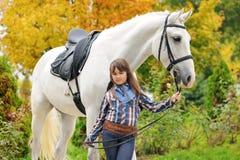 Ung flickaridning på den vita dressyrhästen royaltyfri fotografi