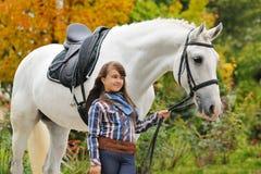 Ung flickaridning på den vita dressyrhästen fotografering för bildbyråer