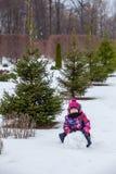 Ung flickarullningen kastar snöboll för en snögubbe på vintern arkivbild