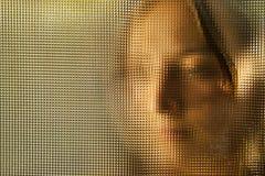 Ung flickas framsida bak exponeringsglas Arkivbild