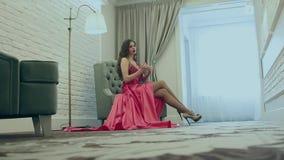 Ung flickasammanträde i en stol lager videofilmer