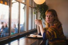 Ung flickasammanträde i ett kafé nära fönstret royaltyfria foton