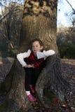 Ung flickasammanträde i trädstam i eftermiddagljus Arkivbild