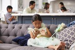 Ung flickasammanträde på det Sofa Using Mobile Phone At hemmet royaltyfri foto