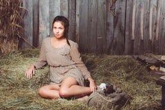Ung flickasammanträde på höet med en säck arkivfoto