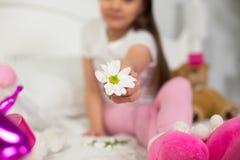 Ung flickasammanträde på hennes säng med blomman Royaltyfria Bilder