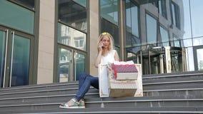 Ung flickasammanträde på momenten med shoppingpåsar som talar på telefonen arkivfilmer