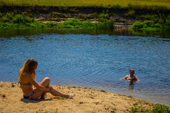 Ung flickasammanträde på sanden på stranden Med hans baksida till kameran Bakgrund fotografering för bildbyråer