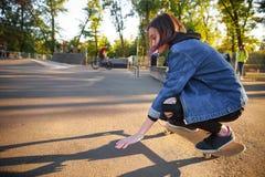 Ung flickasammanträde på skateboarden skateboarding Utomhus livsstil Arkivbild