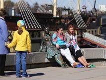 Ung flickasammanträde på statyn på stranden Royaltyfri Fotografi