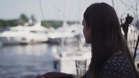 Ung flickasammanträde på terrass av restaurangen på sjösidan Tala med någon lager videofilmer