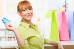 Ung flickashopping med hennes kreditkort och färgglade påsar Arkivfoton