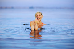 Ung flickashower två ben på havsvatten ytbehandlar arkivfoton