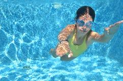 Ung flickasimmaresimning under vatten i pöl och har gyckel, att dyka för tonåring som är undervattens-, familjsemester, sporten o Royaltyfria Bilder