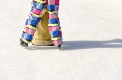 Ung flickaskridskoåkning utomhus på en cirkel med hjälp som lär pingvinet Royaltyfri Fotografi