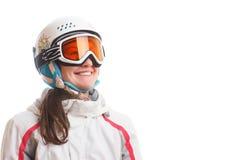 Ung flickasnowboarderen i hjälm och exponeringsglas ser upp och ler Arkivfoton