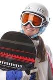 Ung flickasnowboarderen i hjälmen och exponeringsglasen rymmer dess bräde och le Arkivfoto
