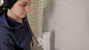 Ung flickaspackel, deg på väggen, och arrangera i rak linje därefter spackeln på väggen med hans hand Reparation släta väggar stock video