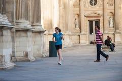 Ung flickaspring längs väggarna av Louvremuseet royaltyfri foto