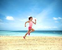 Ung flickaspring på stranden Arkivfoto