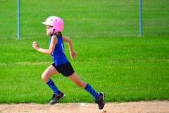 Ung flickaspringbaser i softball Fotografering för Bildbyråer