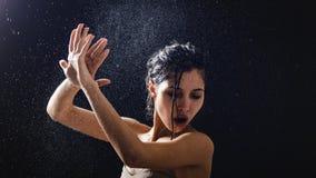 Ung flickastående och plaskande vatten i hennes framsida härlig kvinnlig modell på svart bakgrund royaltyfri foto