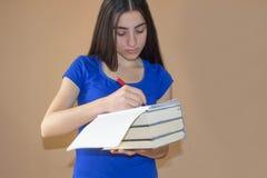 Ung flickastudent med högen av böcker och anmärkningar Information om flickahandstil Royaltyfria Foton